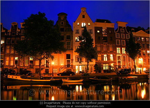 Typical Amsterdam Houses At Night With Reflection In Canal